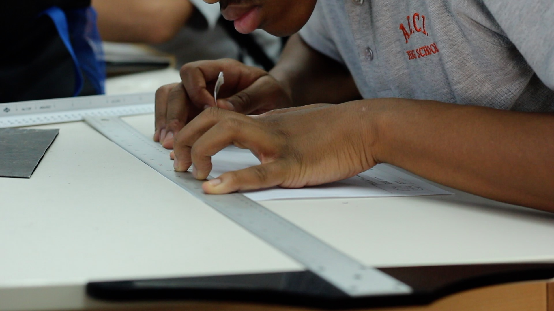 The hands of an A.E.C.I. high school student at work at a drawing table